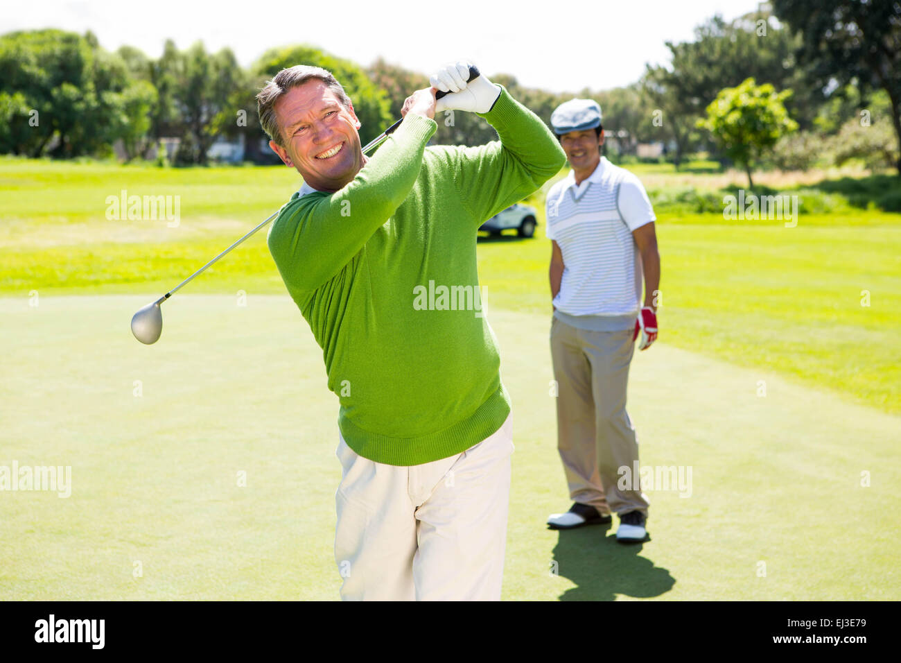 Golfing friends teeing off - Stock Image