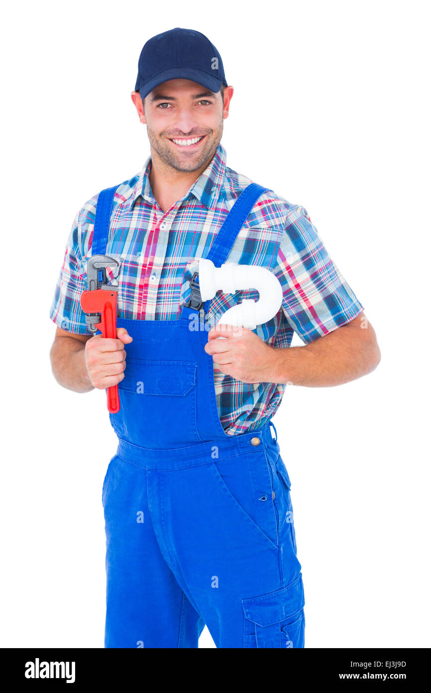 Happy male plumber holding monkey wrench and sink pipe - Stock Image