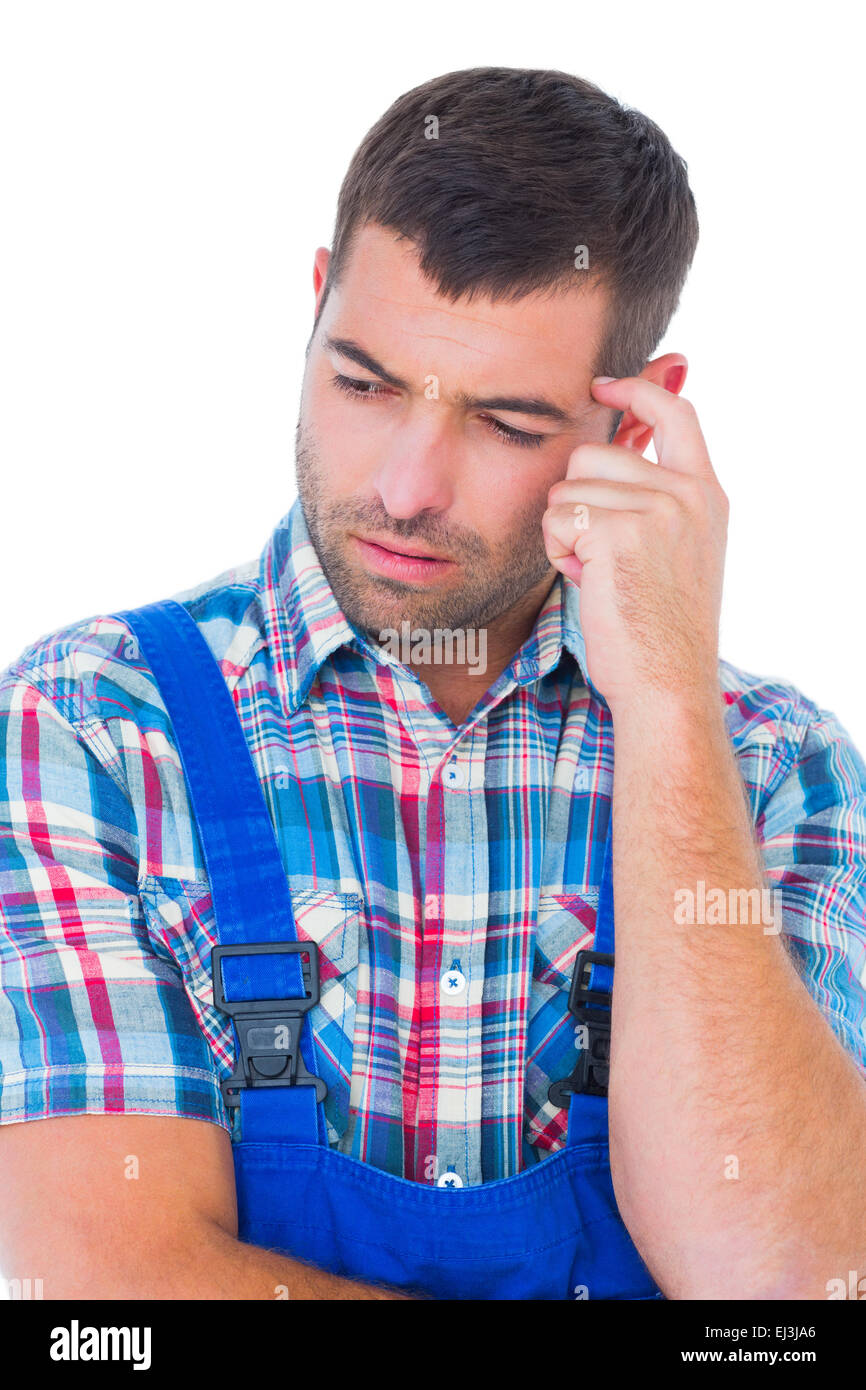 Confused manual worker looking down - Stock Image