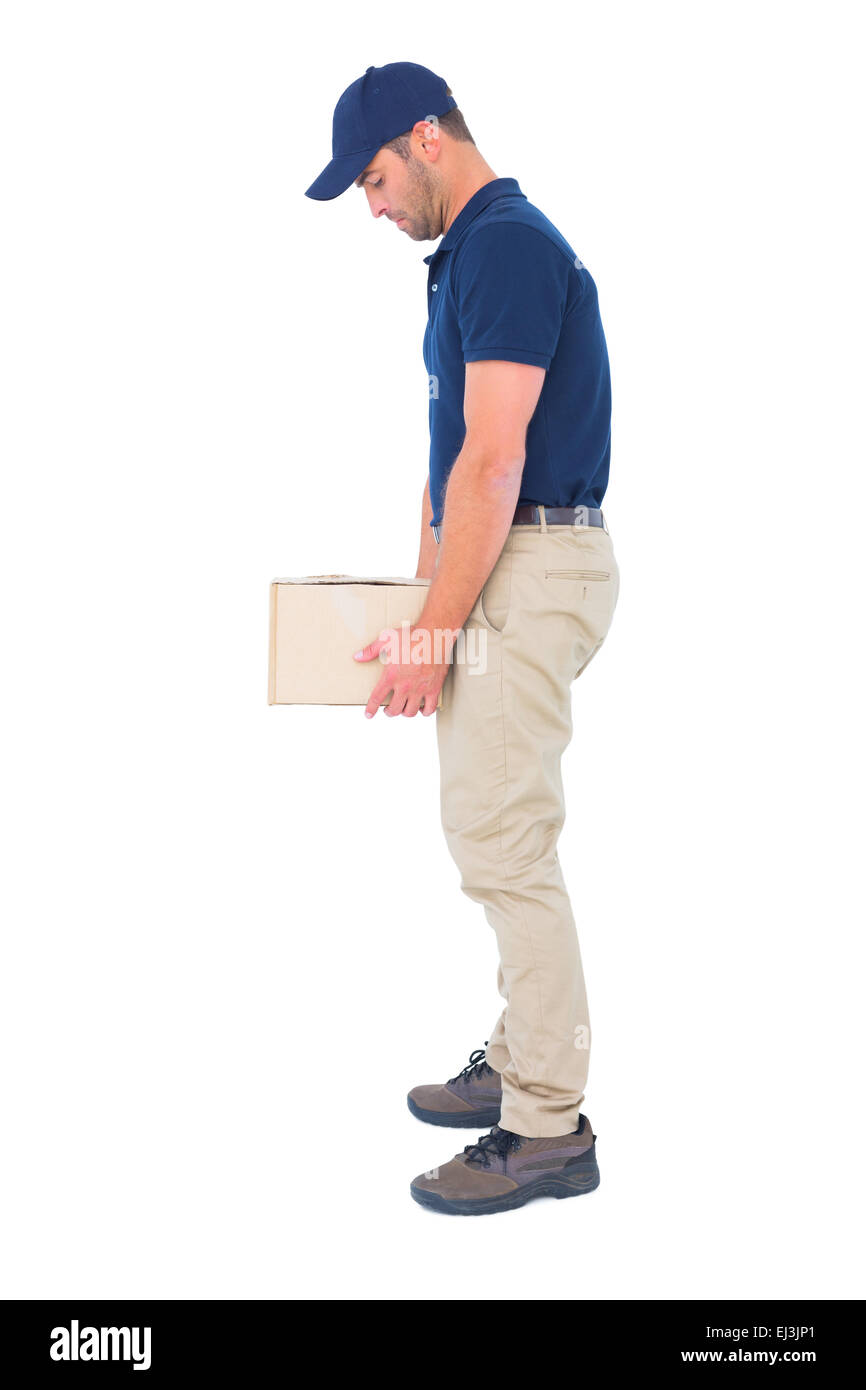 Delivery man carrying heavy package on white background - Stock Image