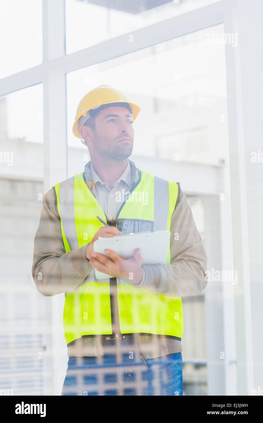 Architect in reflective clothing writing on clipboard at office - Stock Image