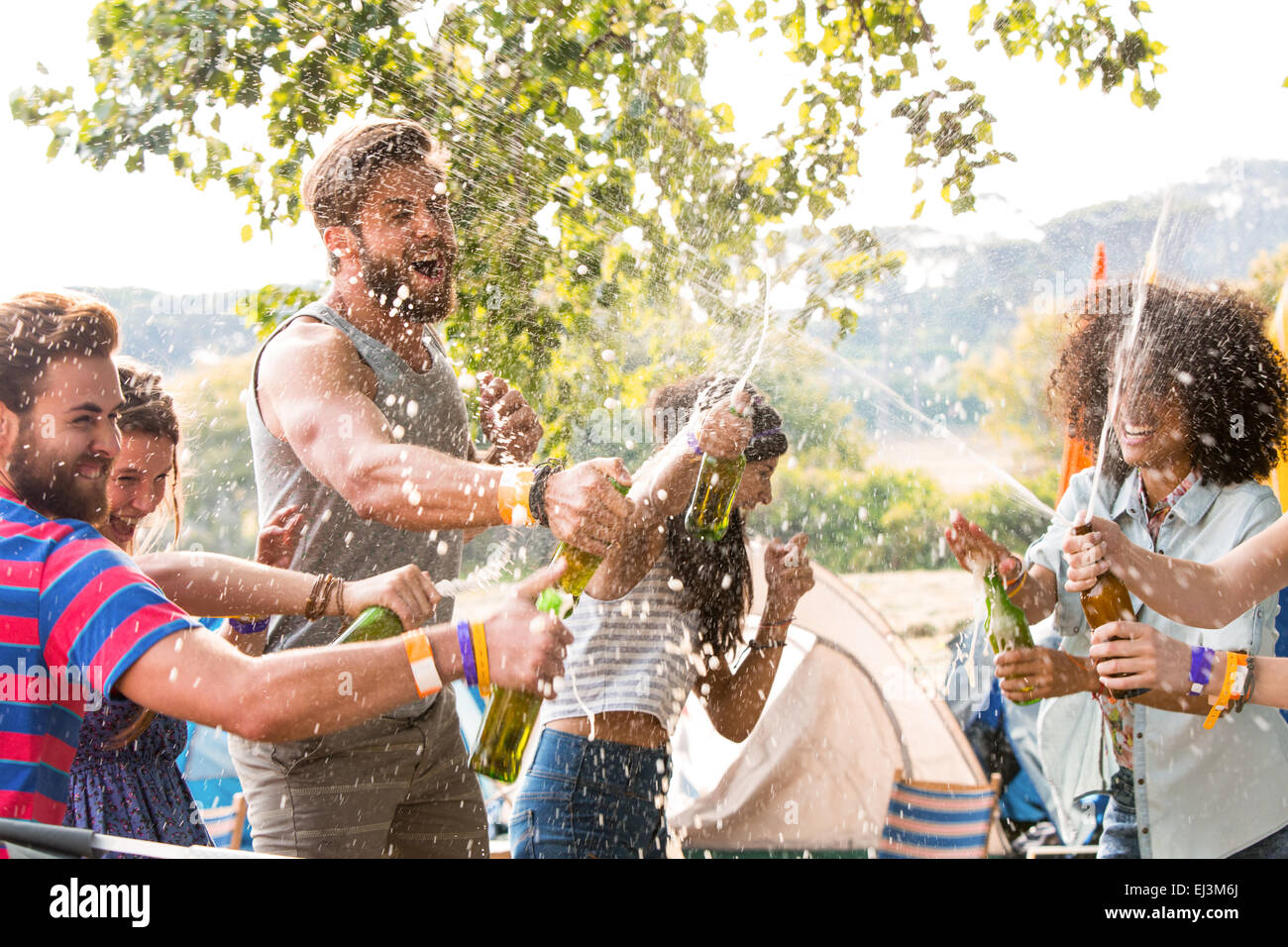 Hipsters spraying beer over each other - Stock Image