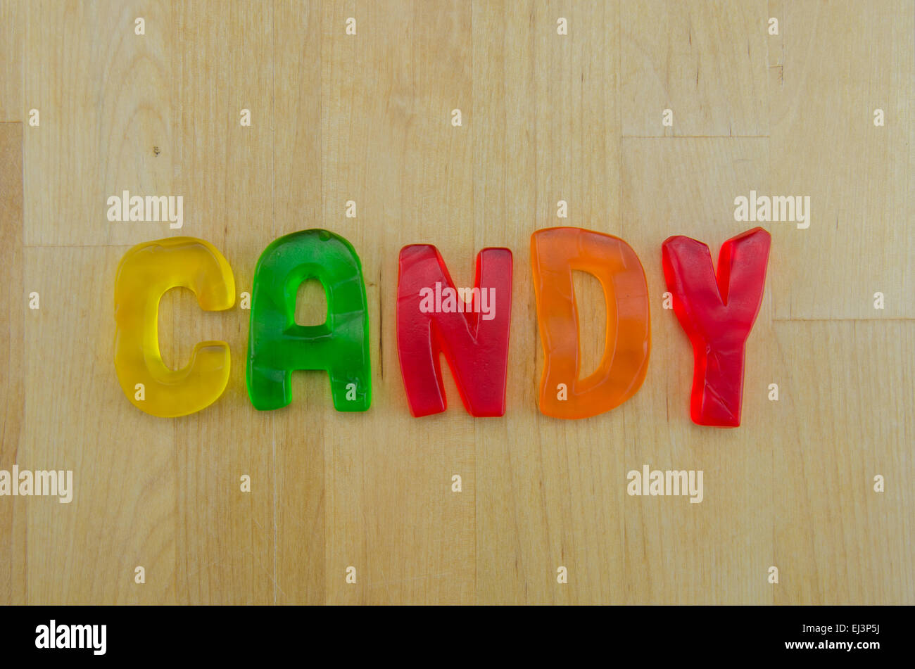 The word candy is spelled out of gummy letters against a butcher block background - Stock Image