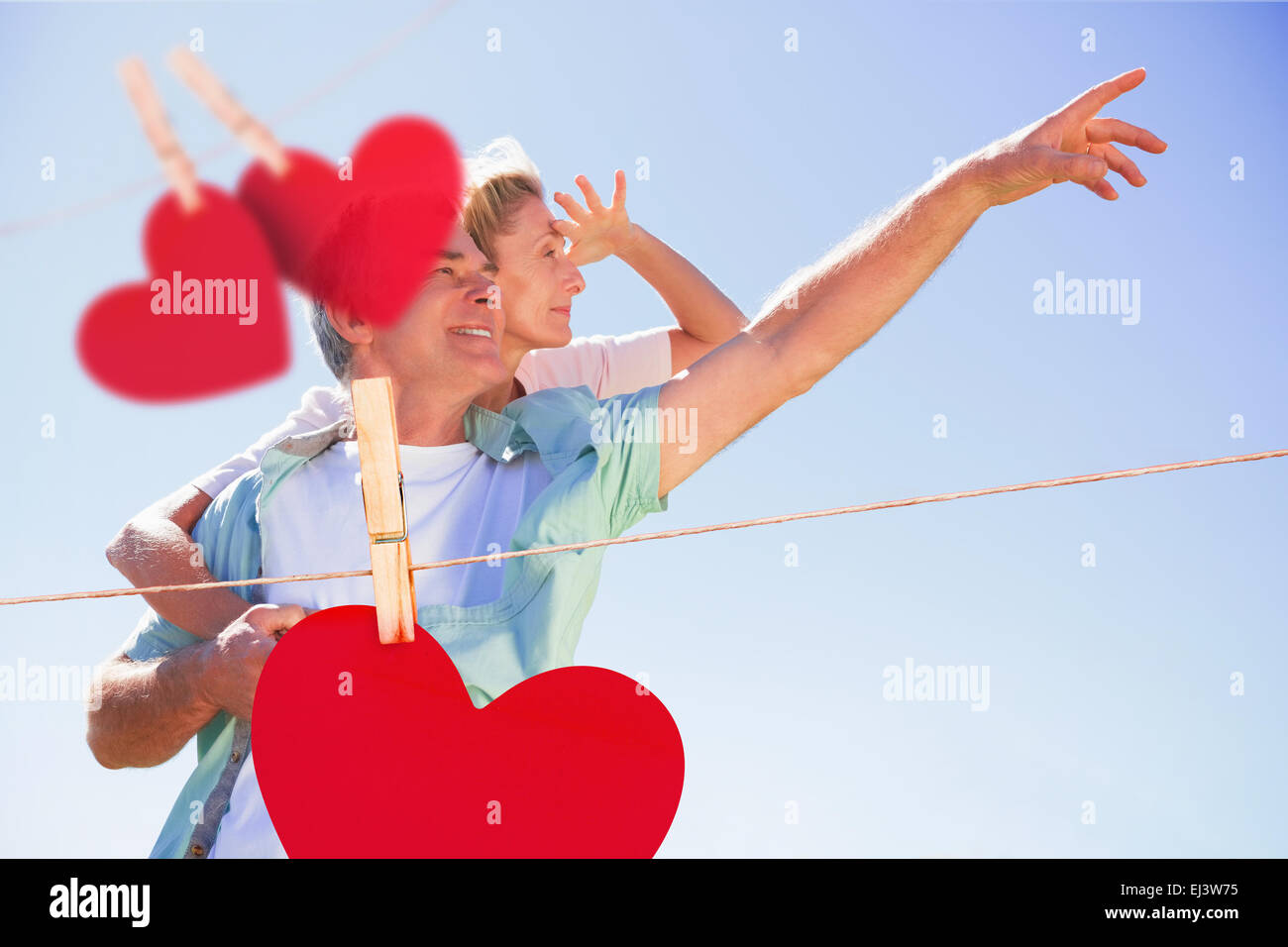Composite image of happy senior man giving his partner a piggy back - Stock Image