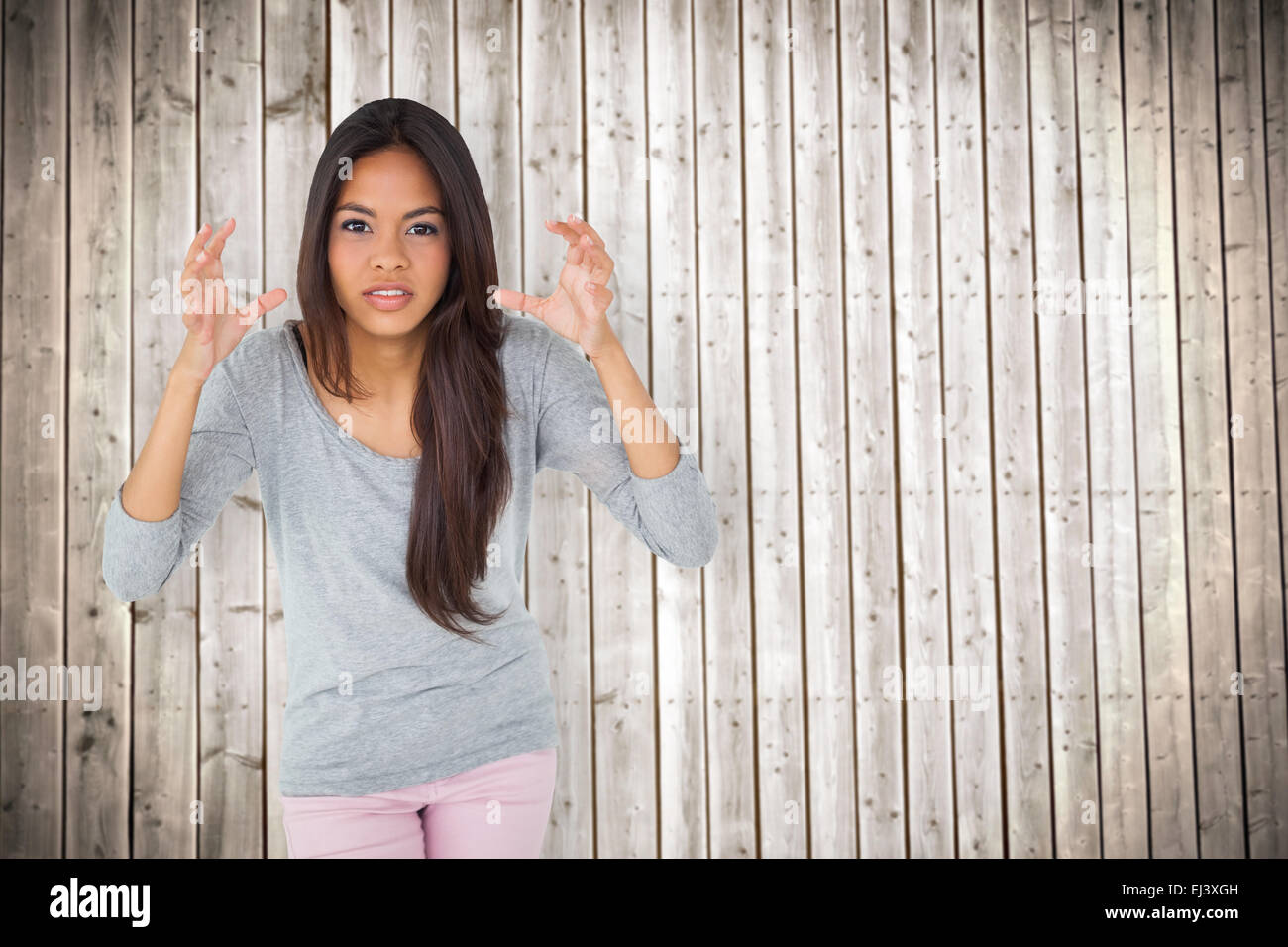 Composite image of angry brunette gesturing - Stock Image