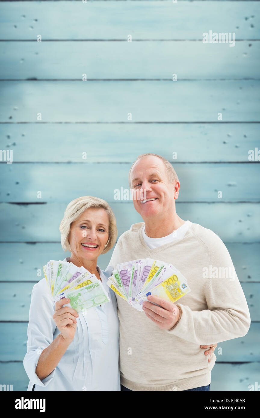 Composite image of happy mature couple smiling at camera showing money - Stock Image
