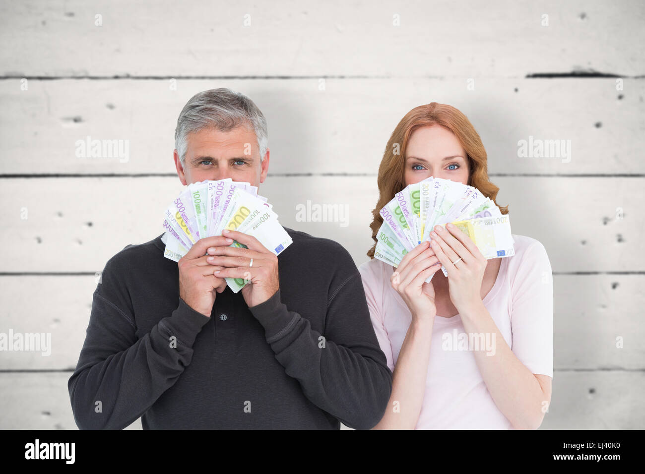 Composite image of casual couple showing their cash - Stock Image