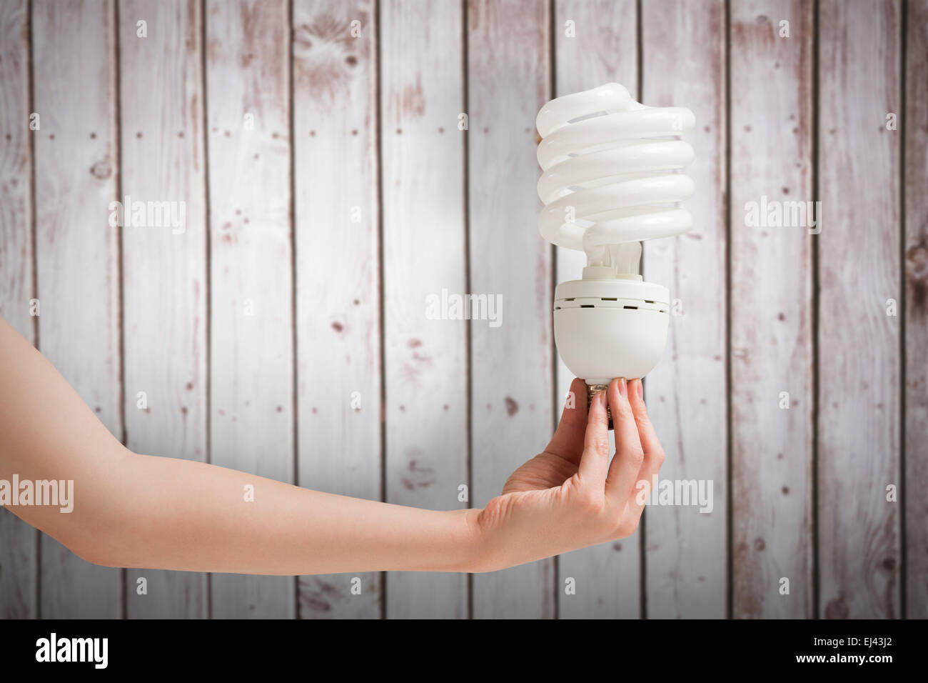Composite image of hand holding energy efficient light bulb - Stock Image