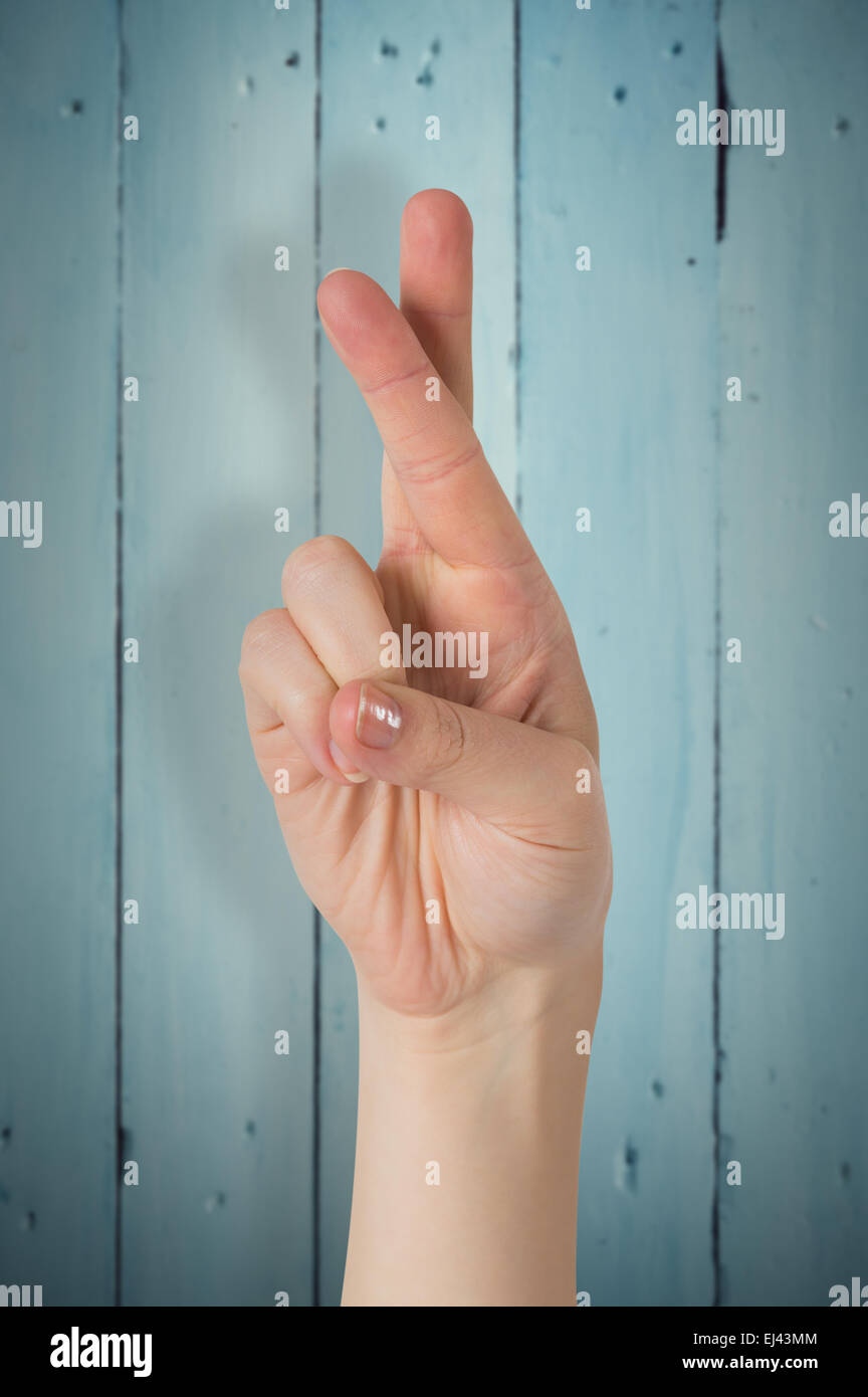 Composite image of hand with fingers crossed - Stock Image
