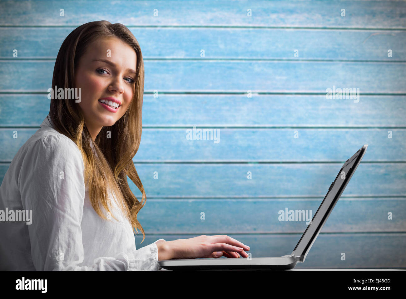 Composite image of businesswoman typing on her laptop Stock Photo