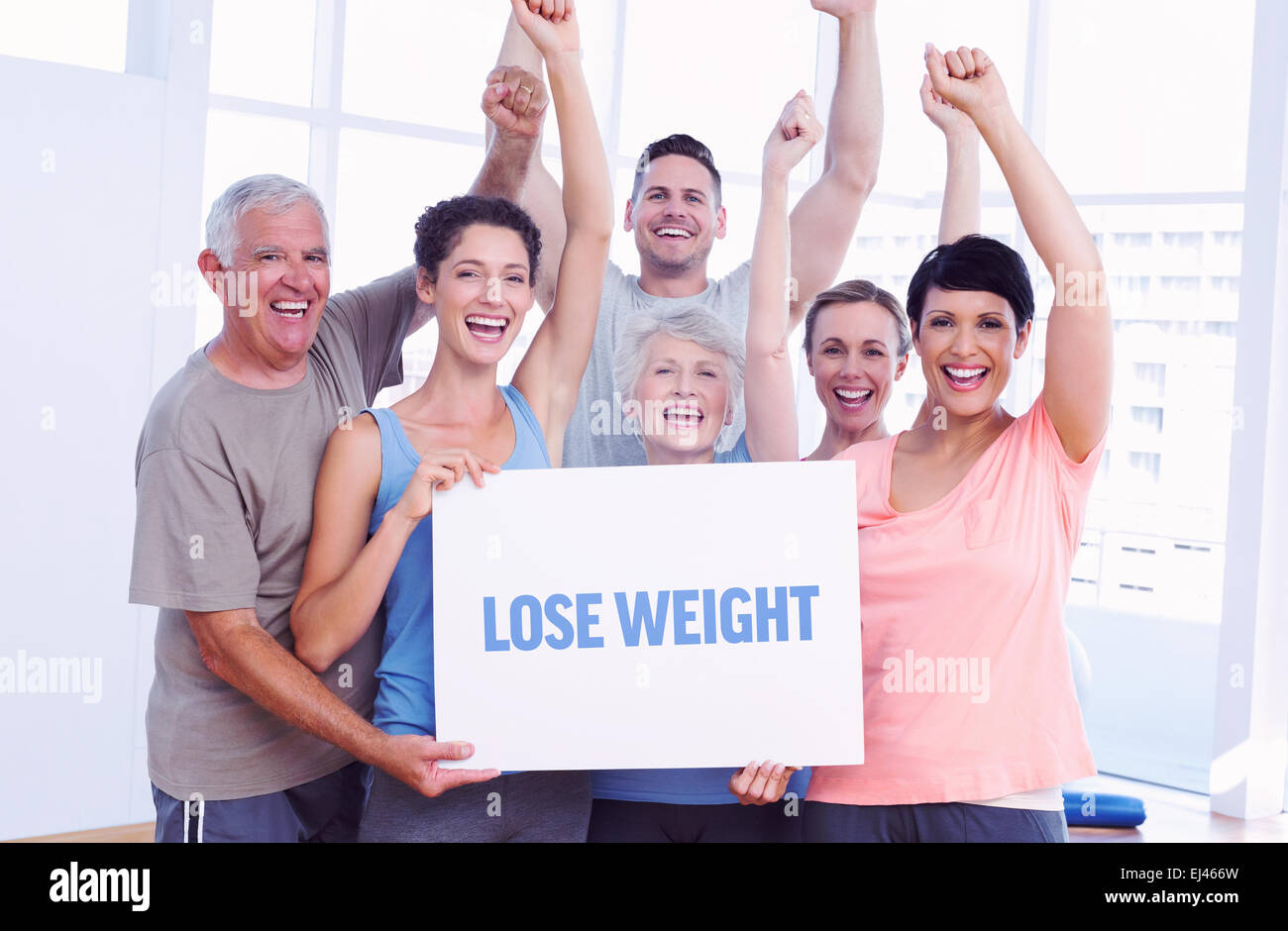 Lose weight against portrait of happy fit people holding blank board - Stock Image