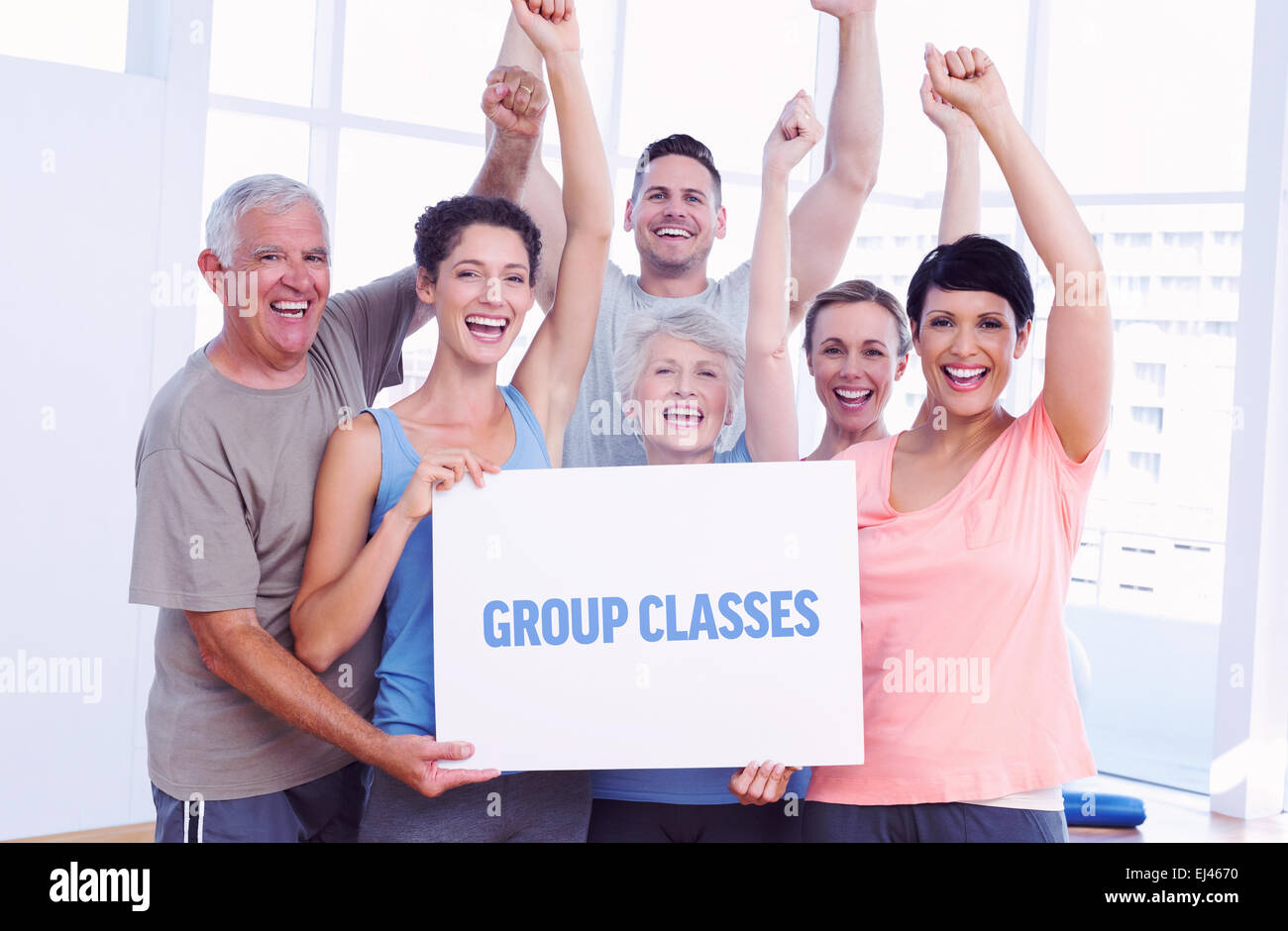 Group classes against portrait of happy fit people holding blank board - Stock Image