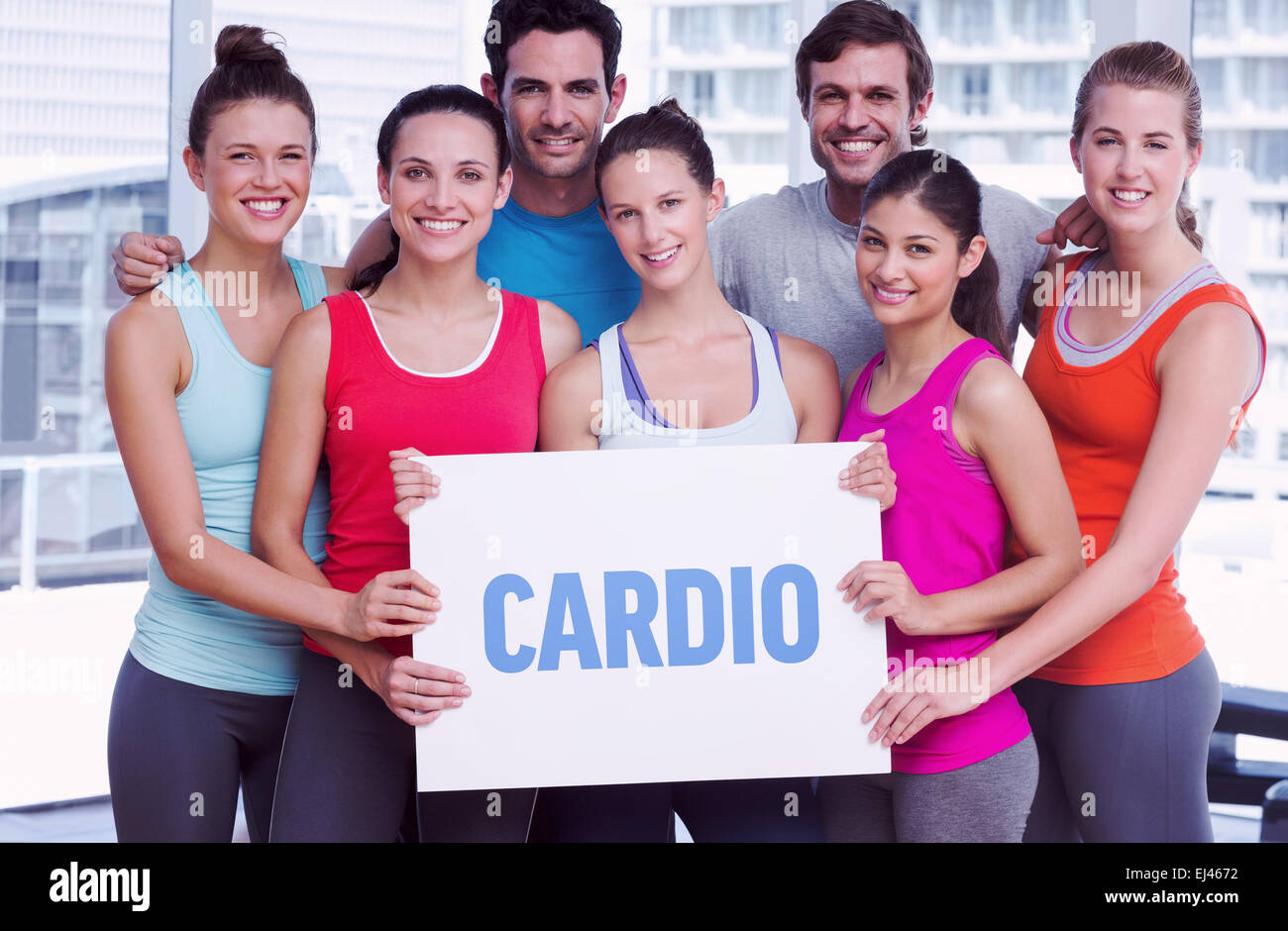 Cardio against fit smiling people holding blank board - Stock Image