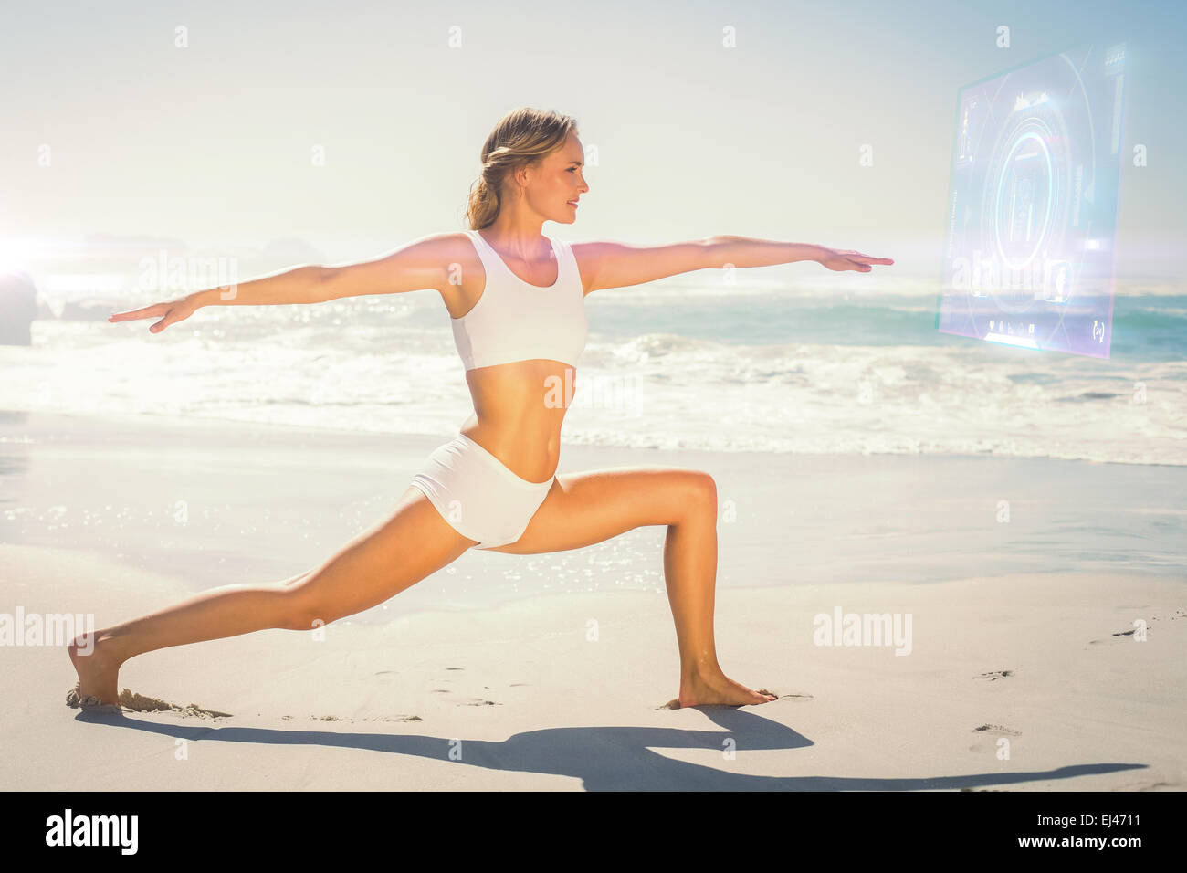 Composite image of gorgeous blonde in warrior pose by the sea - Stock Image