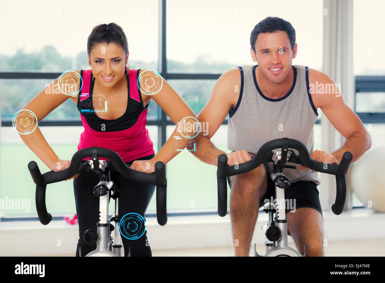 Composite image of young man and woman working out at spinning class - Stock Image