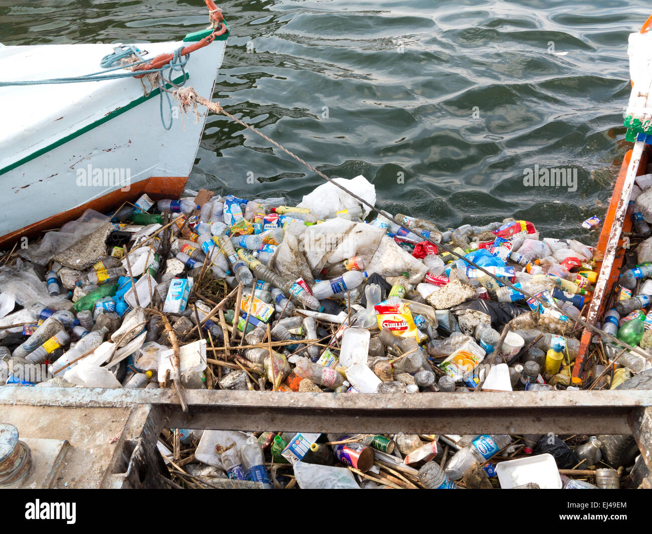 Plastic rubbish floating on the river Nile caught between docked boats and the jetty. Egypt Africa - Stock Image