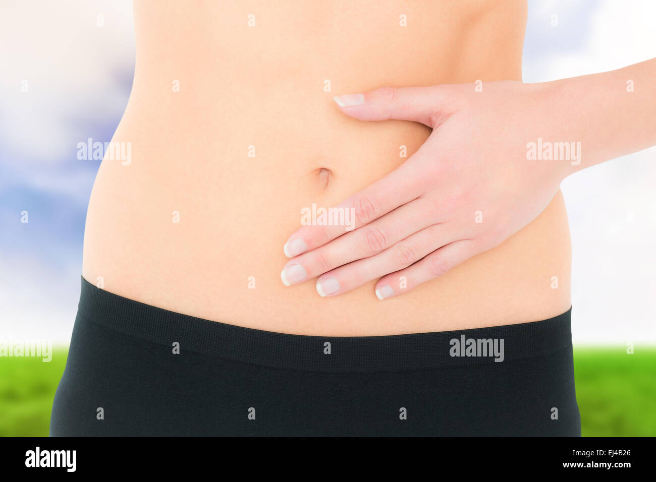 Composite image of closeup mid section of a fit woman with stomach pain - Stock Image