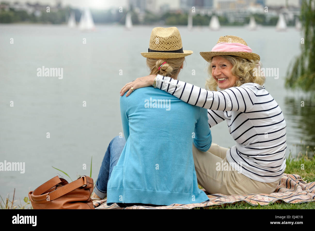 Mother and daughter sitting at the riverside - Stock Image