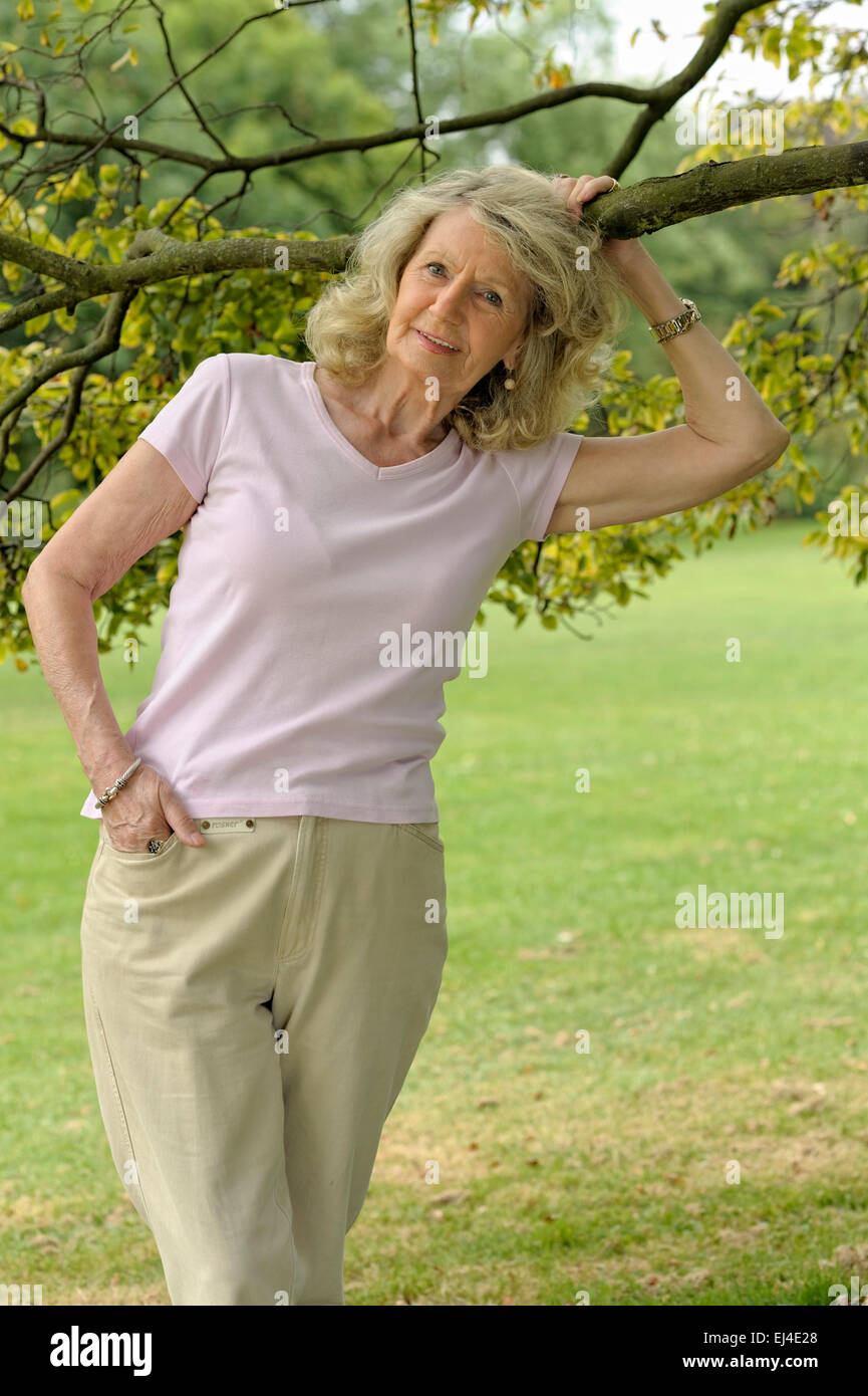 Elderly woman leaning against a tree - Stock Image