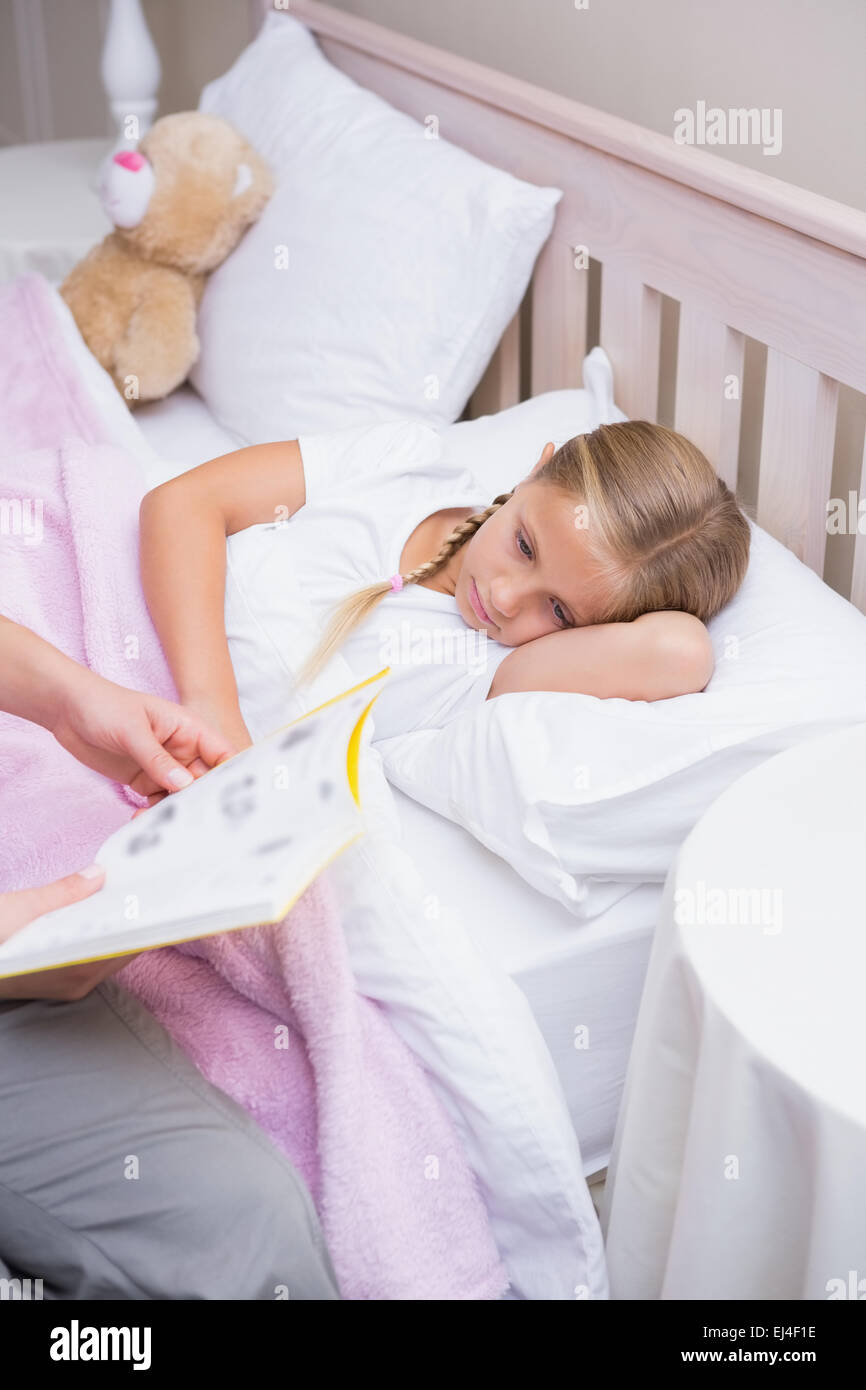 Mother reading daughter a bedtime story - Stock Image