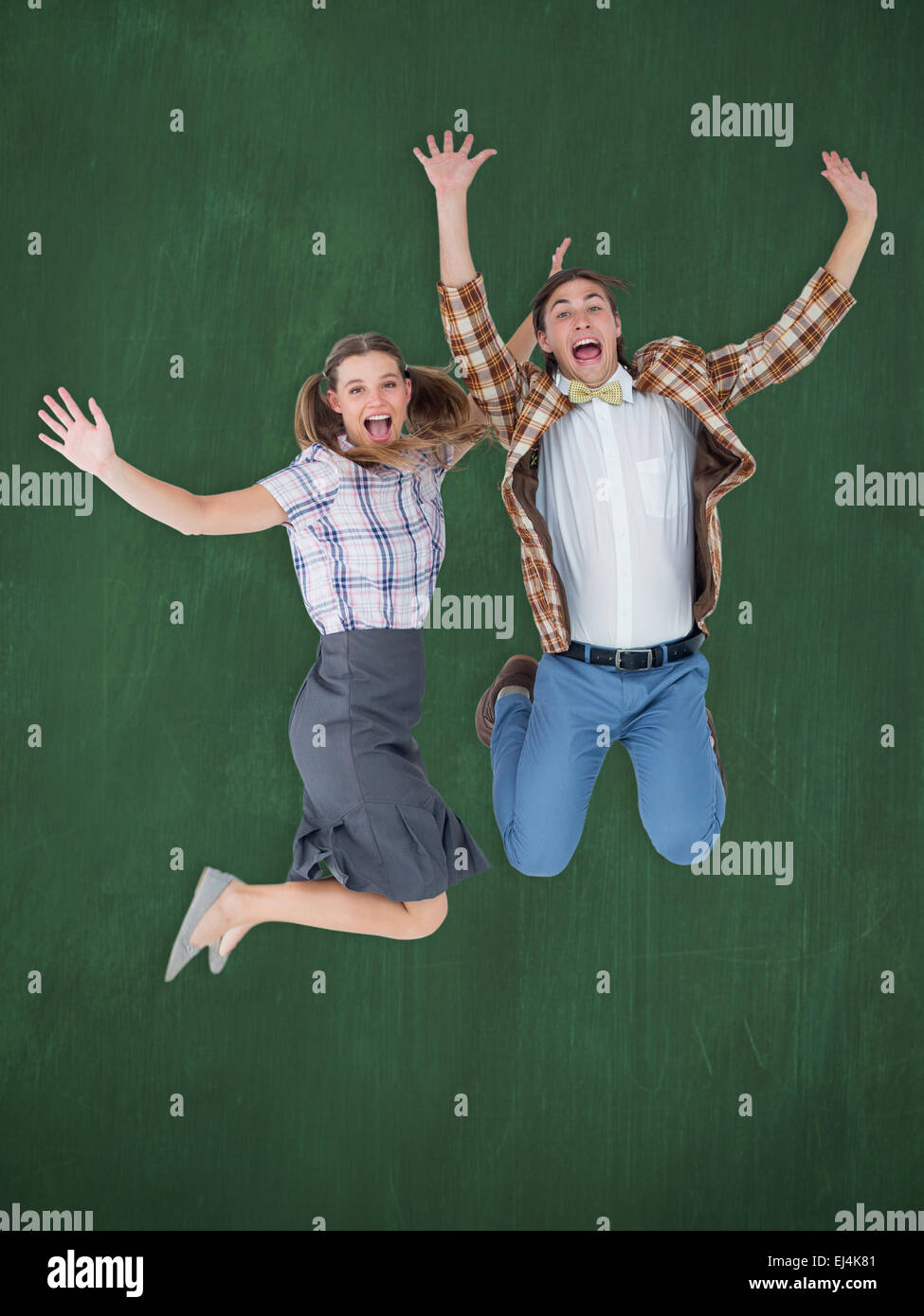 Composite image of geeky hipsters jumping and smiling - Stock Image