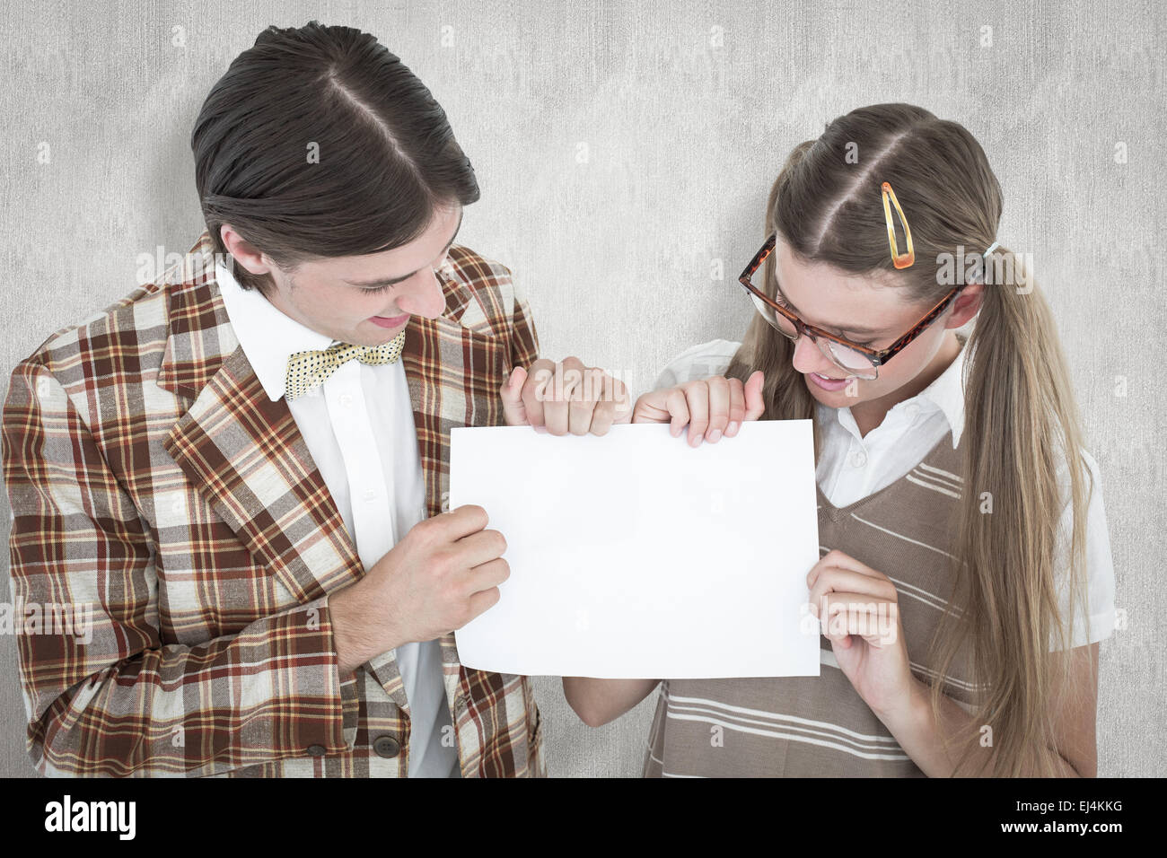 Composite image of geeky hipsters holding a poster - Stock Image