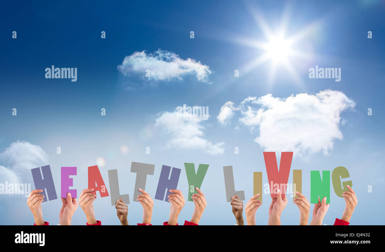 Composite image of hands holding up healthy living - Stock Image