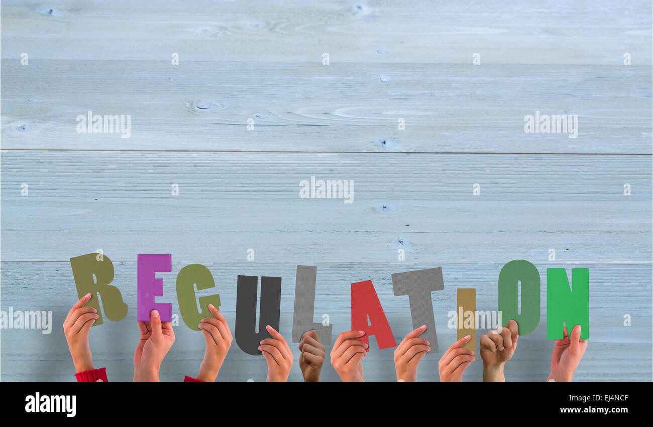 Composite image of hands holding up regulation - Stock Image