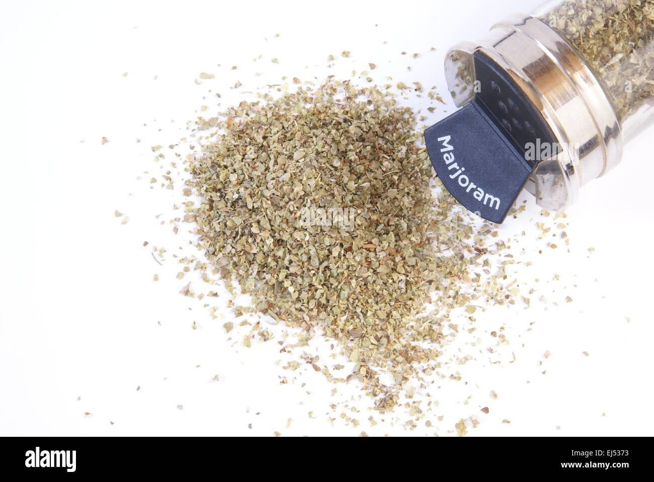 Dried marjoram spice on a white background with glass spice jar next to it. - Stock Image