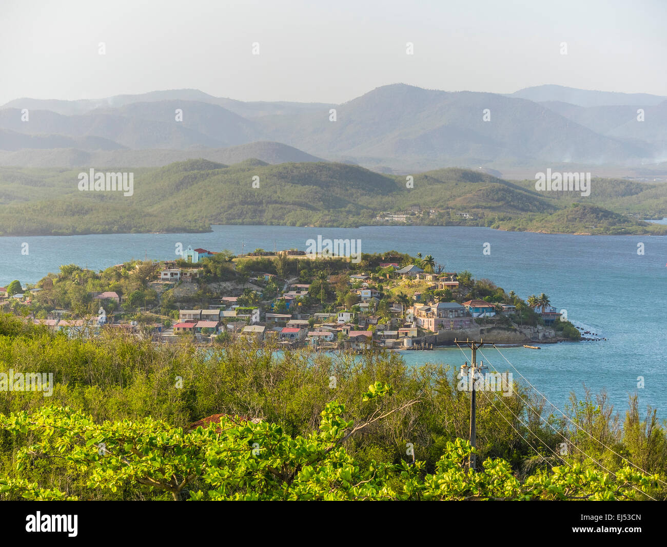 An overall view of tiny Cayo Granma Island by Santiago de Cuba from a viewpoint on the mainland above the island. - Stock Image