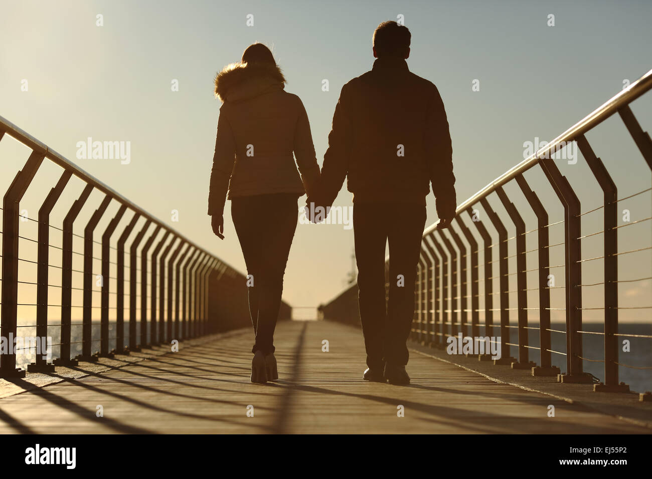 Back silhouette of a couple walking holding hands on a bridge in the beach at sunset - Stock Image