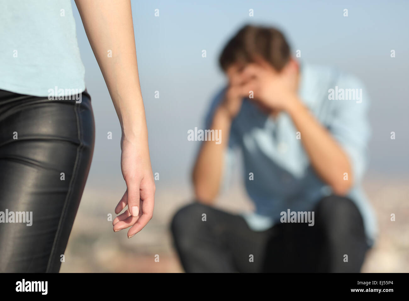 Breakup of a couple with a sad man in the background and the girlfriend leaving him in the foreground - Stock Image