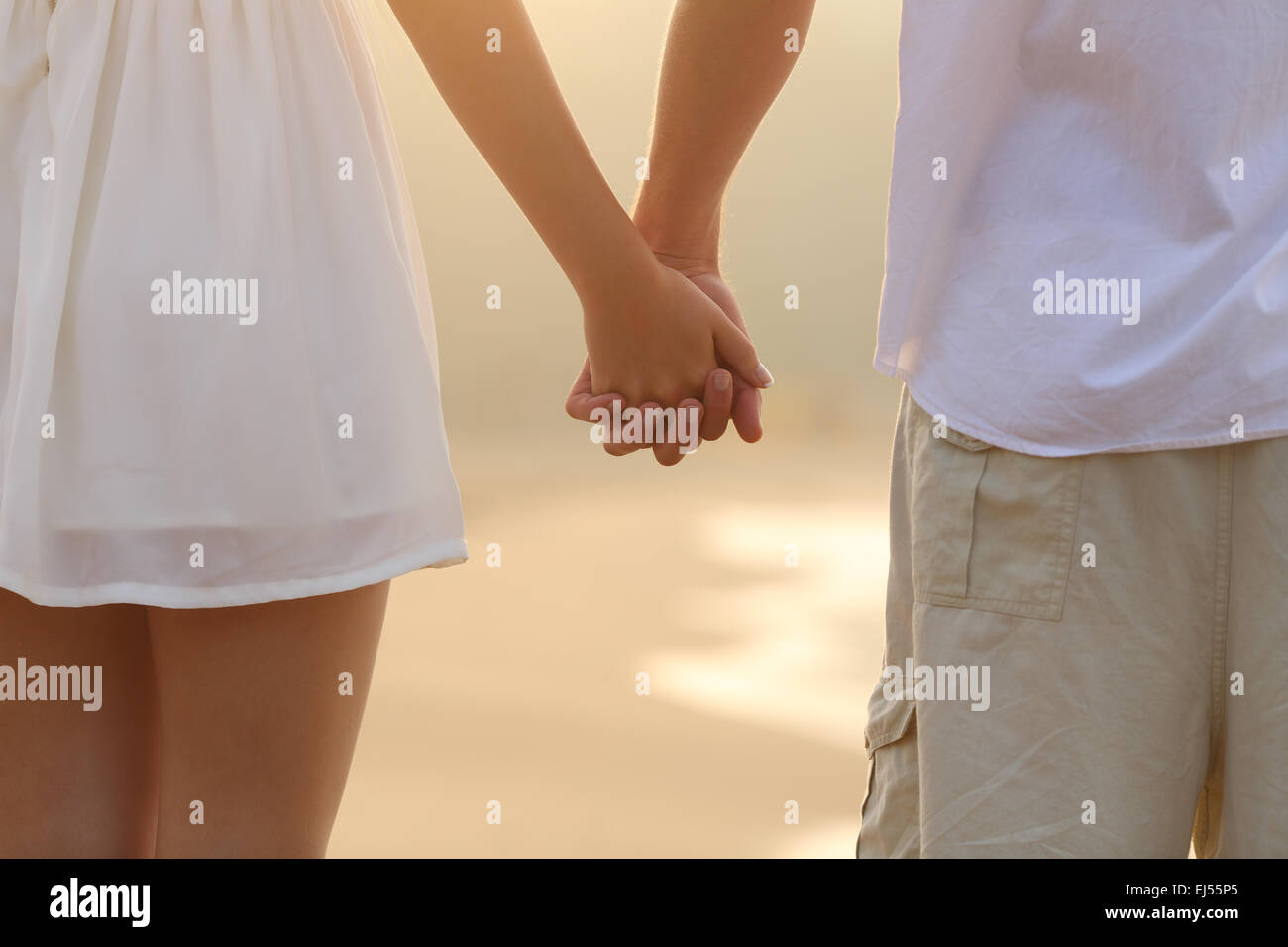Close up of a back view of a couple walking and holding hands on the beach at sunrise - Stock Image