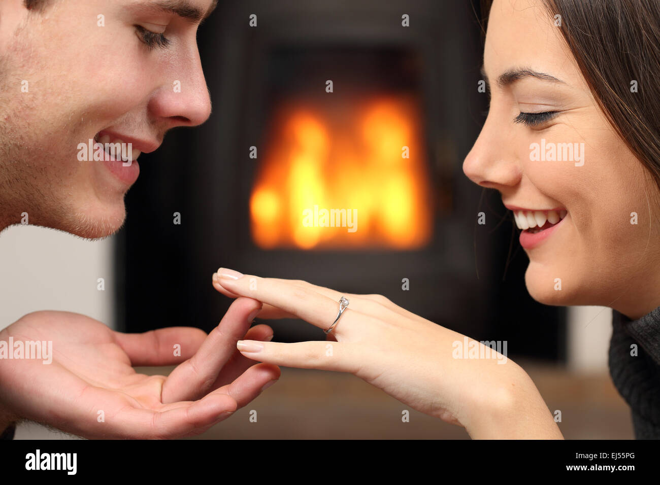 Couple looking a engagement ring after proposal at home with a fire place in the background - Stock Image