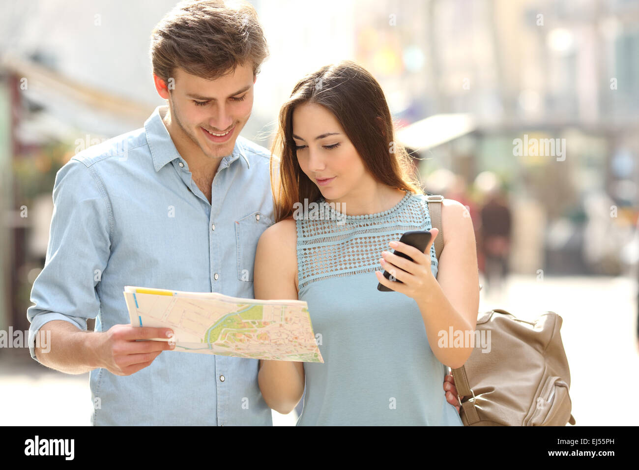 Couple of tourists consulting a city guide and mobile phone gps in a street - Stock Image
