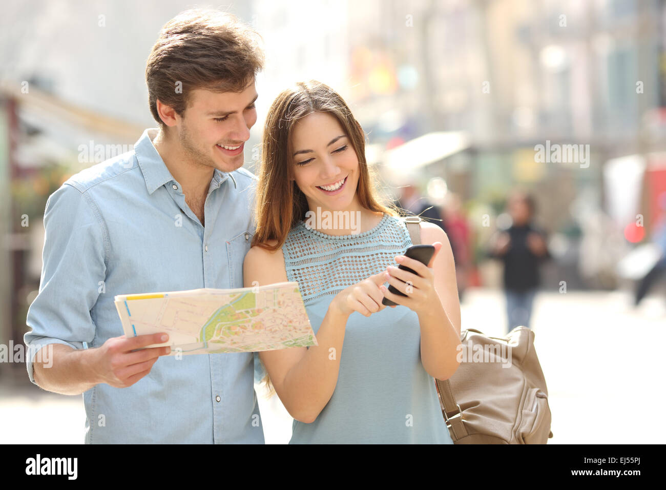 Couple of tourists consulting a city guide and smartphone gps in the street searching locations - Stock Image