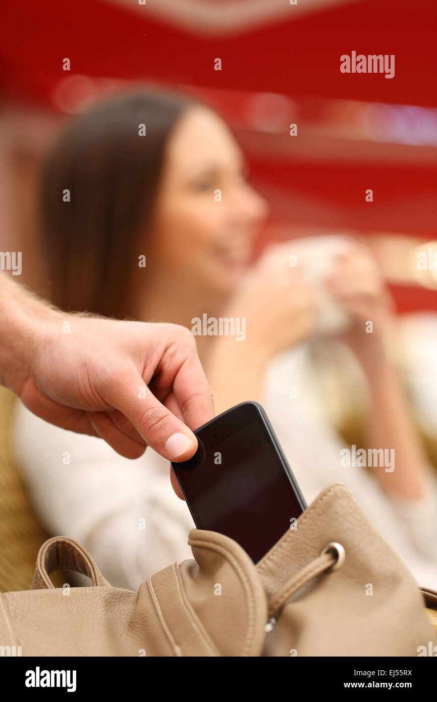 Thief hand stealing a mobile phone from a woman bag while she is relaxed - Stock Image