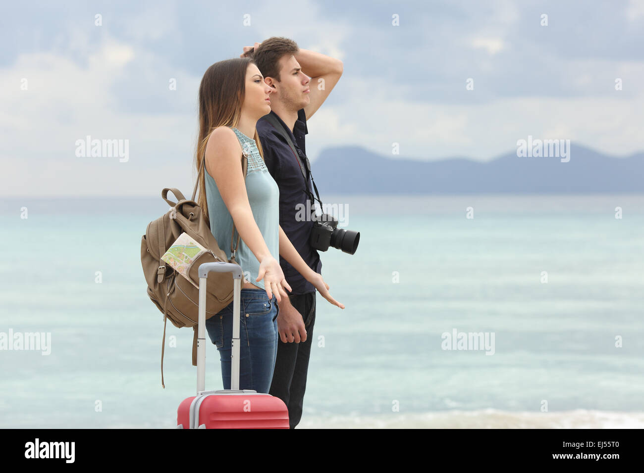 Tourists frustrated with the bad weather when arrive to the beach with the cloudy sky in the background - Stock Image