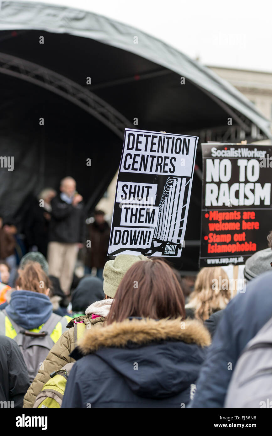 London, 21st March 2015 Anti-racism protesters watch a speaker at a rally in Trafalgar Square holding placards - Stock Image