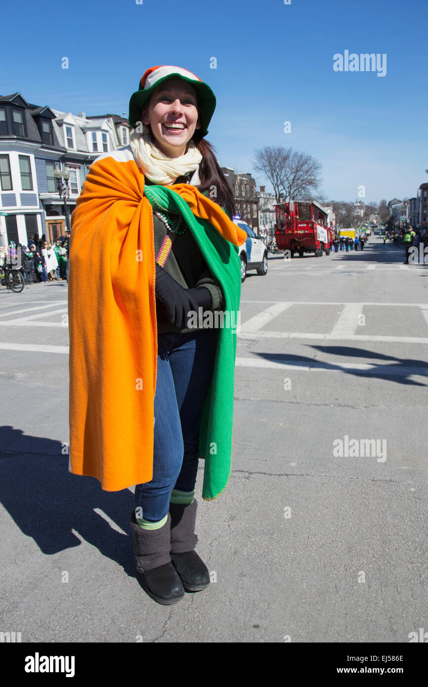 Smiling woman draped with Irish flag, St. Patrick's Day Parade, 2014, South Boston, Massachusetts, USA - Stock Image