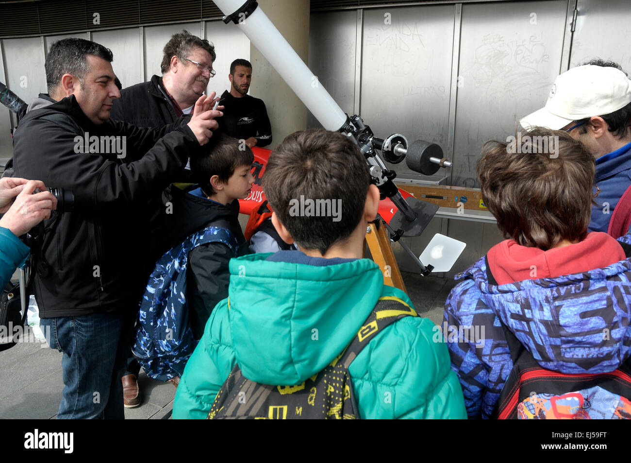 Man explaining to children how works an amateur telescope to watch the solar eclipse in Barceloneta beach, Barcelona - Stock Image