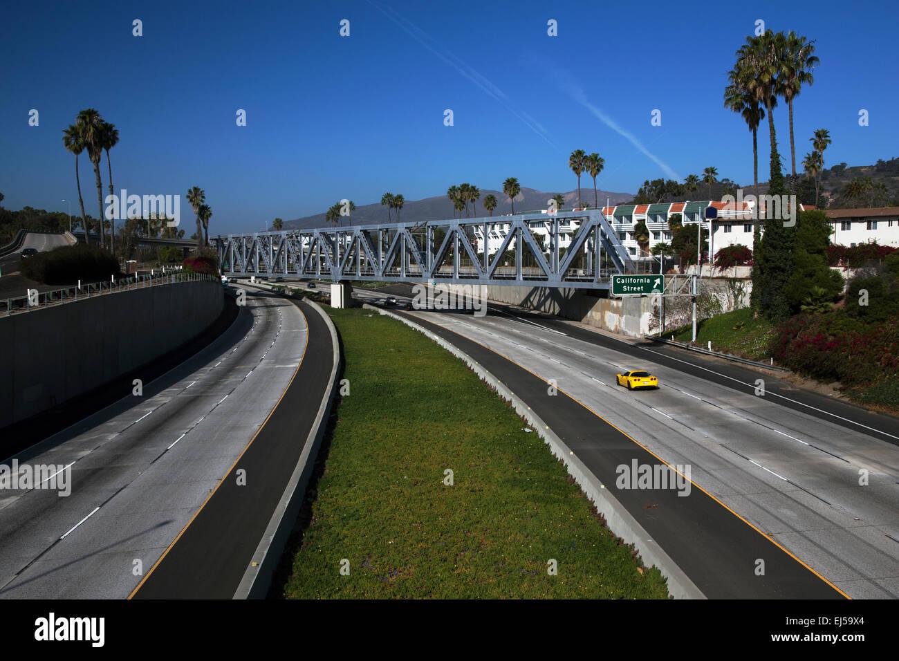 Yellow Corvette drives Route 101 at California Avenue, Ventura, California, USA - Stock Image
