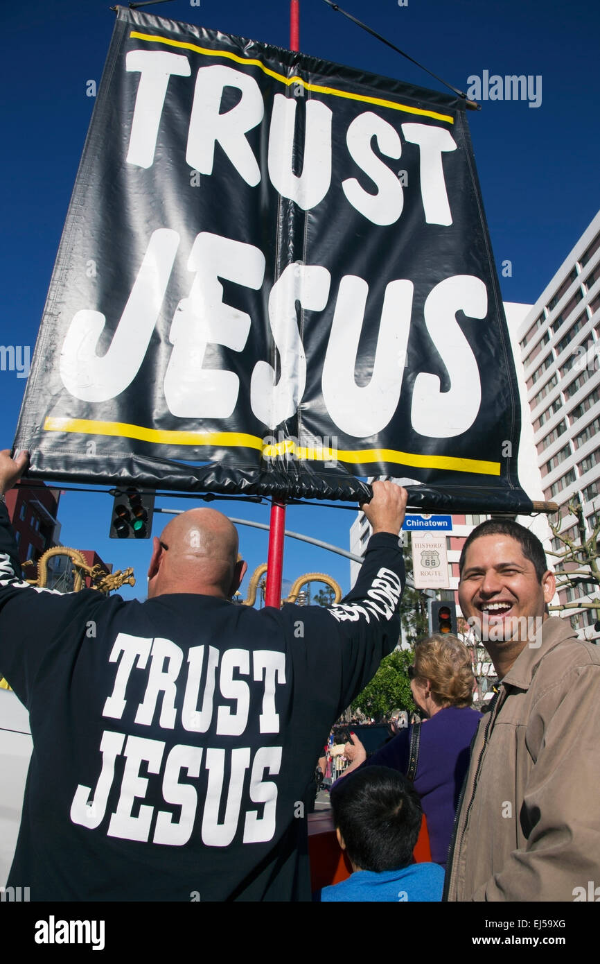 Sign reads 'Trust Jesus' sign and man mocking him, Chinese New Year, Los Angeles, California, USA - Stock Image