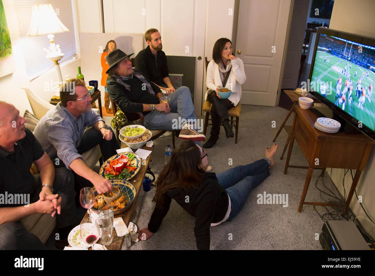 Group of people watch NFL Superbowl XLVIII on television, Feb. 2, 2014, Denver Broncos vs. Seattle Seahwaks - Stock Image