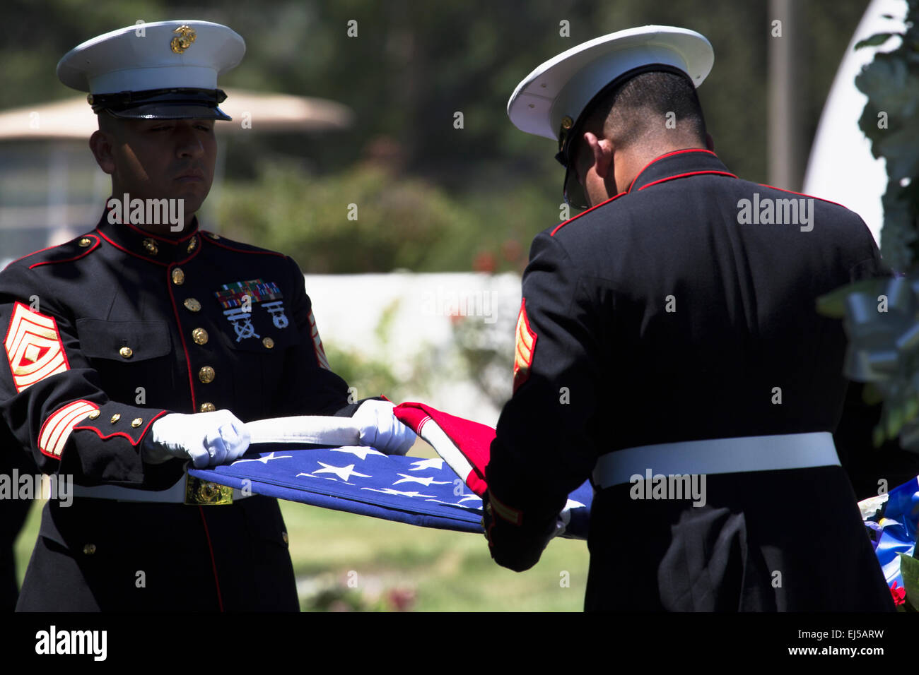 Marine folds flag at Memorial Service for fallen US Soldier, PFC Zach Suarez, 'Honor Mission' on Highway - Stock Image