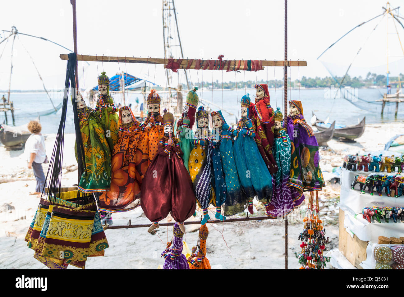 Typical traditional colourful marionette puppets on display for sale as tourist souvenirs on the beach at Fort Cochin, Stock Photo