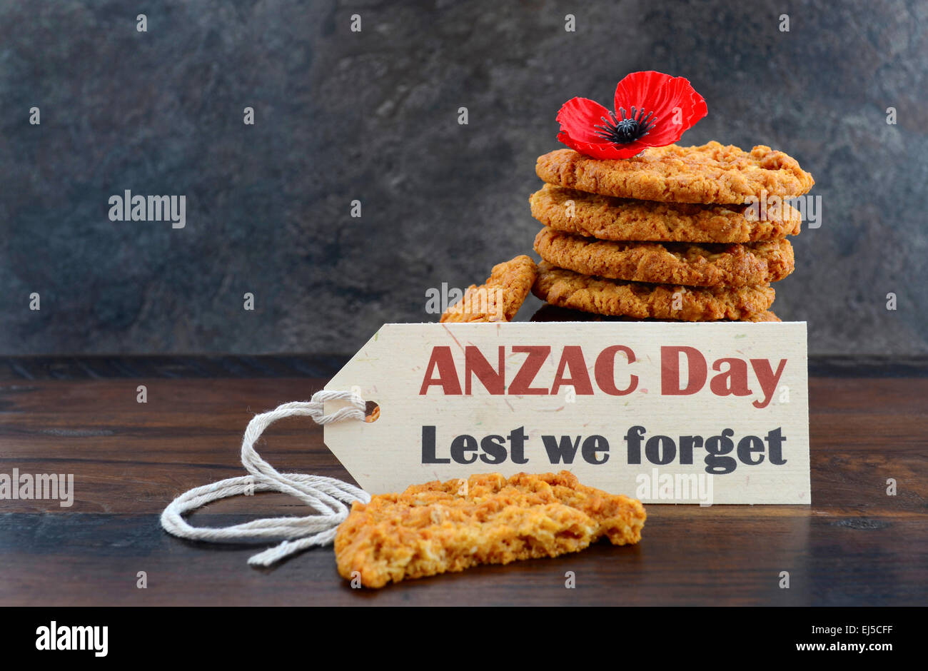 Australian Anzac biscuits with Anzac DAy, Lest We Forget message on dark wood and slate background. - Stock Image