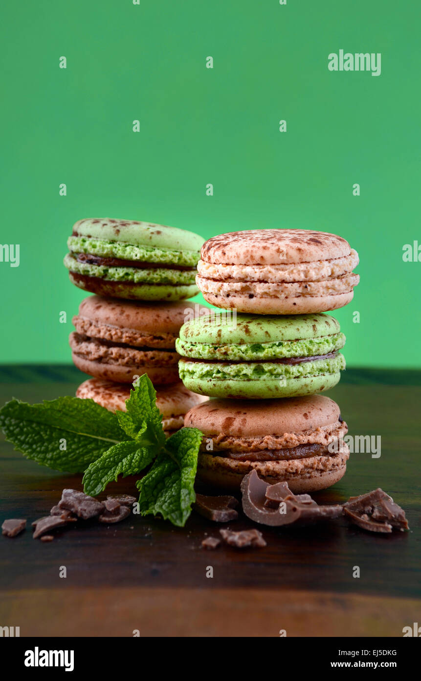 Chocolate and mint flavor macaroons on dark wood table and green background. - Stock Image