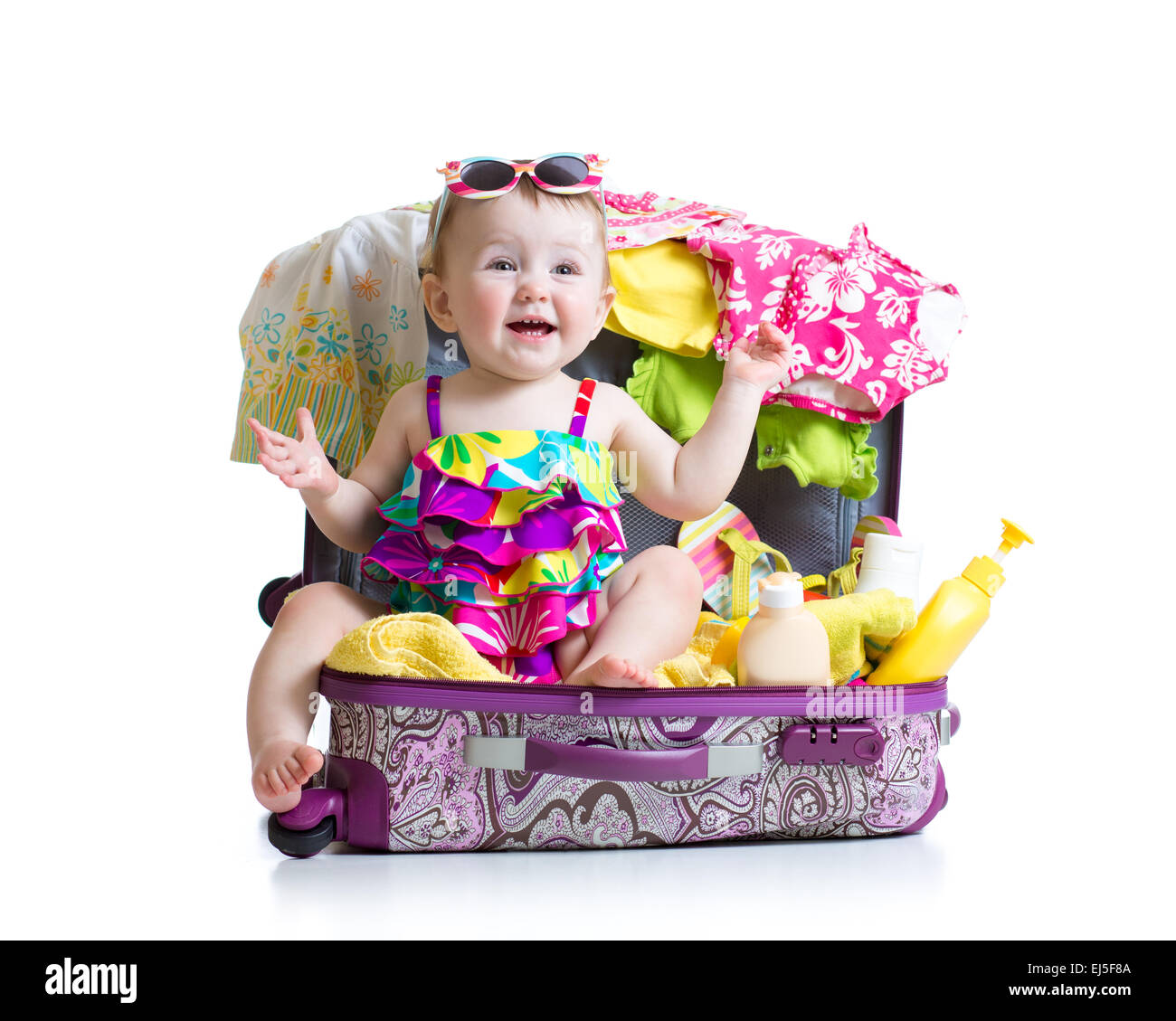Baby girl sitting in trunk with things for vacation travel - Stock Image