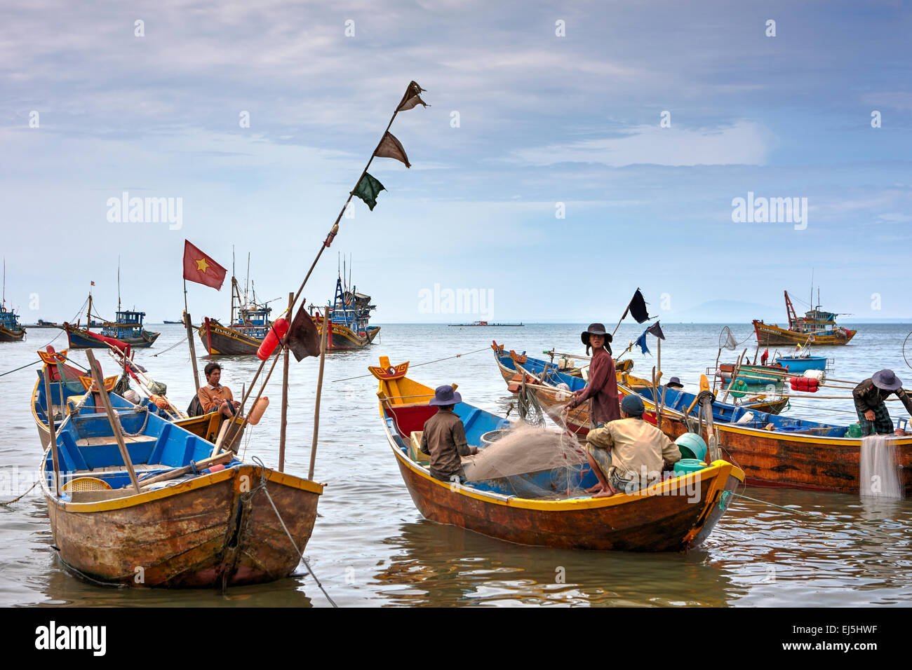 Vietnamese fishermen on traditional wooden boats at Mui Ne Fishing Harbour. Mui Ne, Binh Thuan Province, Vietnam. - Stock Image